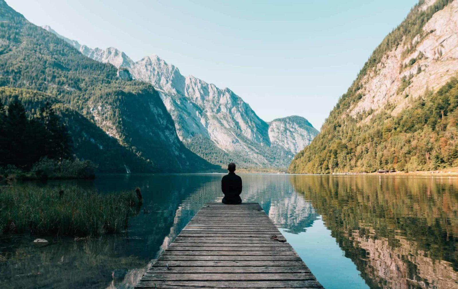mann auf steg an einem bergsee